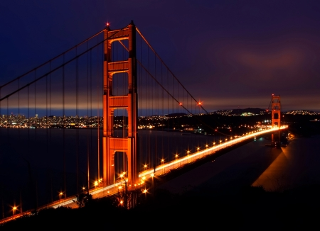 Night scene with Golden Gate Bridge and San Francisco lights in far background photo