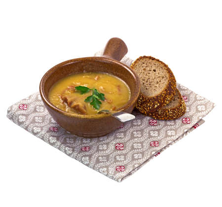 Bowl of yellow pea soup and rye bread on napkin  Isolated