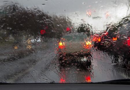 Road view through car window with rain drops
