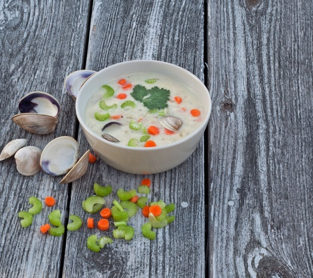 chowder: Bowl of clam chowder soup on reclaimed wood background Stock Photo