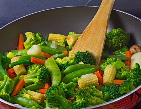 Close-up of frying pan with stir fry vegetables and wooden spoon
