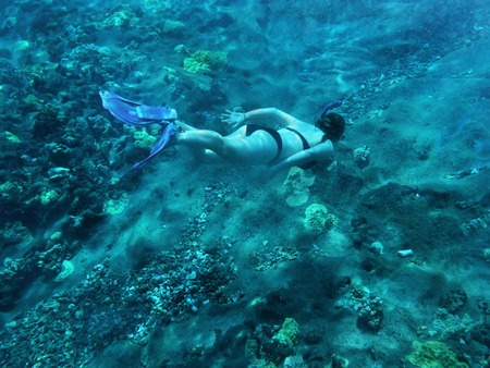 Woman snorkeling in turquoise water near coral reef