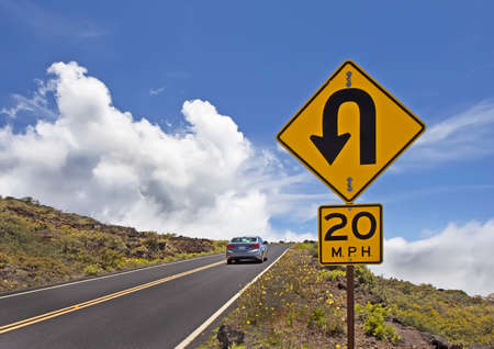 sky is the limit: Mountain road with car and traffic signs Stock Photo