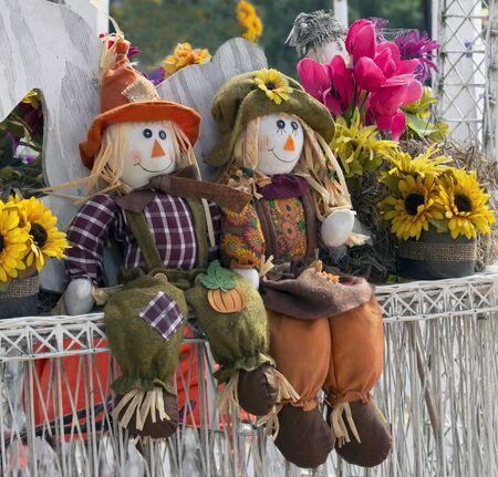 autumn scarecrow: Two autumn scarecrows sitting at the fence. Autumn decorations
