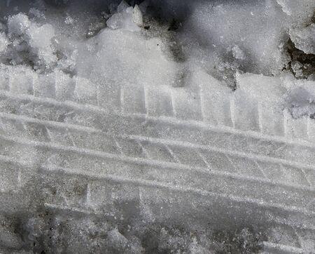 Close-up van natte sneeuw met bandensporen