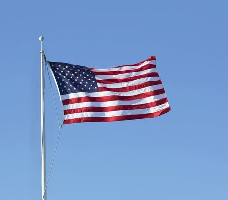USA flag flying in the wind on blue sky background