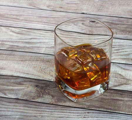 reclaimed: Closeup of a glass of whisky with ice cubes on  reclaimed wood background Stock Photo