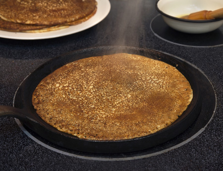 Frying pan with hot sourdough crepe on the stove top. Imagens