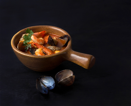 Close up of seafood stew cioppino on black wooden background.