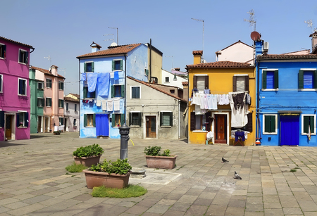 Street with colorful houses and drying clothes in Burano, Italy