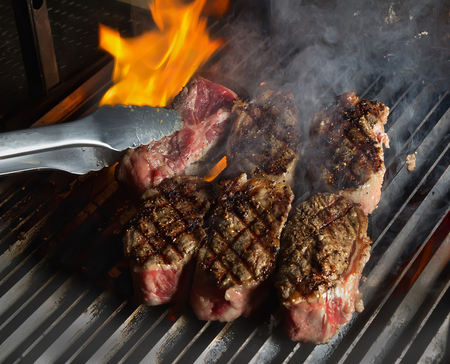 Closeup of steaks on hot grill with flame.