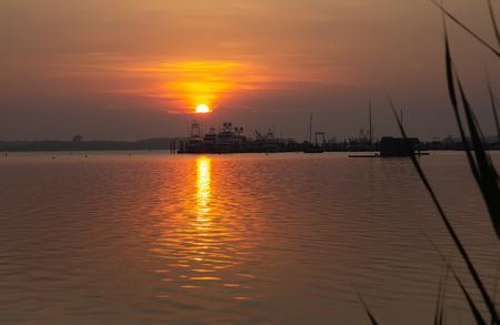 Landscape with lake, boats and sunset sky at Lake Montauk, New York, USA
