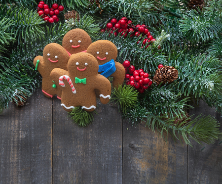 Handmade gingerbread cookies with christmas tree branches with red berries and pines on old wood background. Imagens