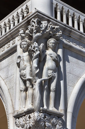 VENICEITALY - APRIL 13, 2018: Sculpture of Adam and Eve separated by a tree and Satan's snake in the corner of Doges palace.   Editorial