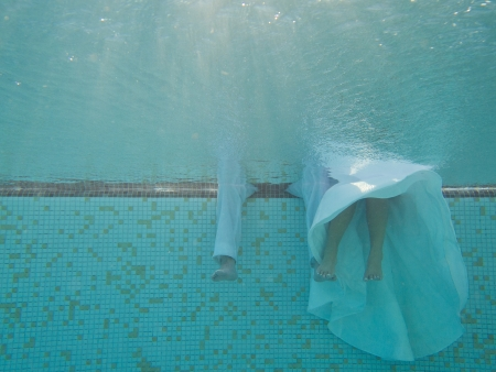 Bride and groom sit on the edge of a swimming pool during a trash the dress session   Stock fotó