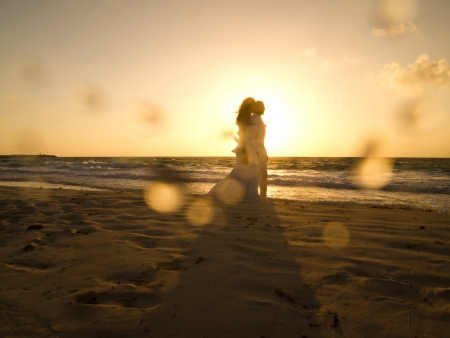A bride and groom walk on the beaches of Puerto Morelos, Mexico shortly after sunrise   版權商用圖片