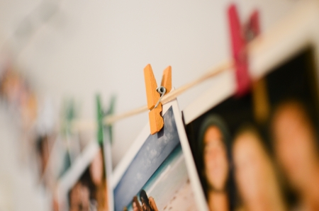 hold up: Wooden pins hold up polaroid photographs   Stock Photo