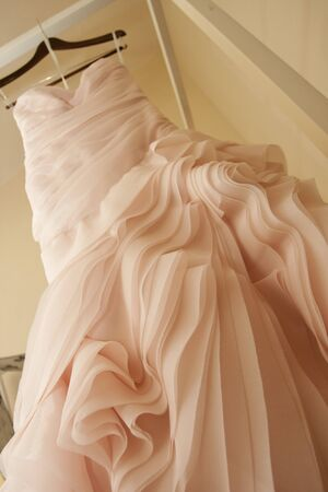 four poster: A pink wedding dress hangs from a four poster bead   Stock Photo