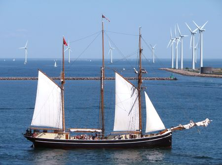 wind power past & future - tall ship with wind turbines in background