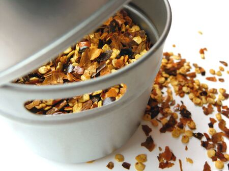 close-up kitchen spice tin of crushed red pepper on a white surface Stock Photo