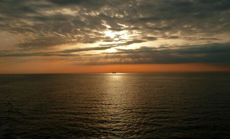 orange sunset and rays over ship on ocean