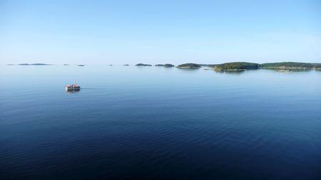 small boat alone on calm sea of blue