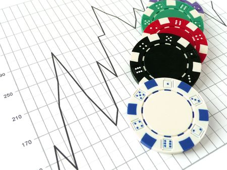 poker chips sitting on a stock market graph