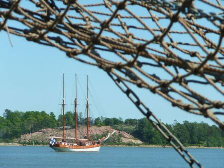 distant tall ship sailing out with blurred rigging ropes in foreground Stock Photo