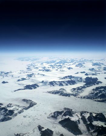 Earth view above greenland glaciers and mountains beneath horizon of black space. Stock Photo