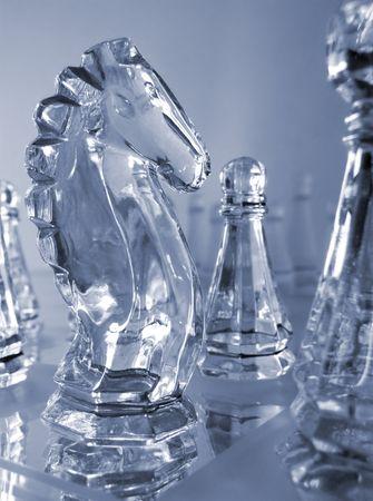 helder glas ridder en pion stuks in blauw op gespiegelde schaakbord