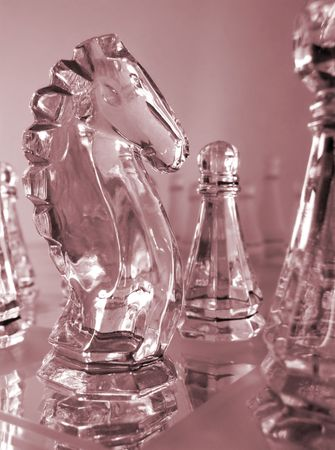 clear glass knight and pawn pieces in red on mirrored chess board