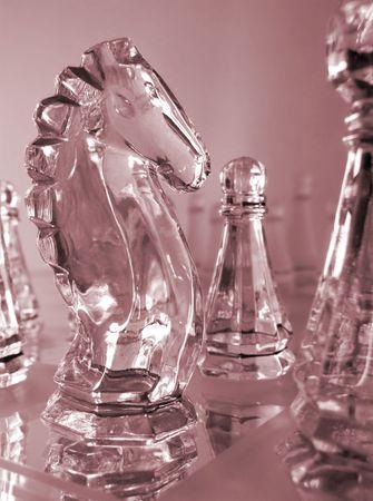 Schakel de knight and pawn stukken glas in het rood op mirrored schaak bord