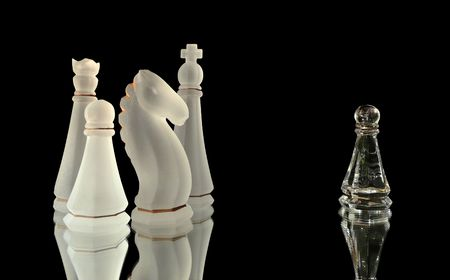 apart: single pawn standing apart from a crowd of chess pieces isolated on black Stock Photo