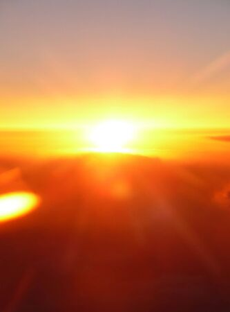 beautiful orange sunset view flying above the clouds Stock Photo