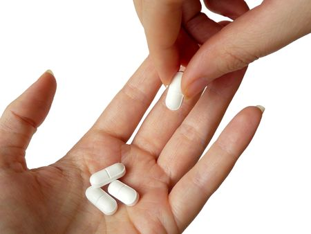 passing over: hand holding white pills in palm with second hand adding a pill to the pile