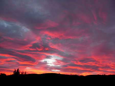 intense pink sunset over the silhouette of trees on a hill
