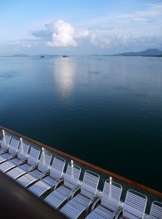 lounge chairs on the deck of a cruise ship overlooking ocean Stock Photo