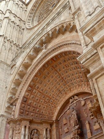 close-up detail of the doorway and glass rose window facade of Palma Cathedral
