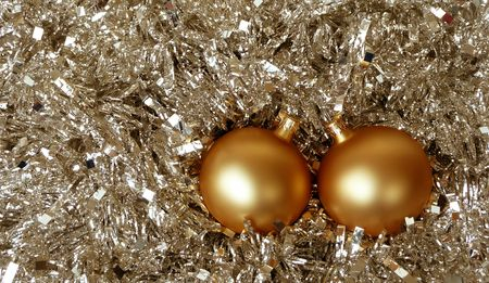 pair of gold christmas tree balls in background of silver xmas tinsel Stock Photo
