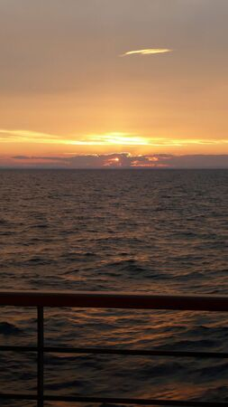 view looking over cruise ship railing to the golden glow of an ocean sunset