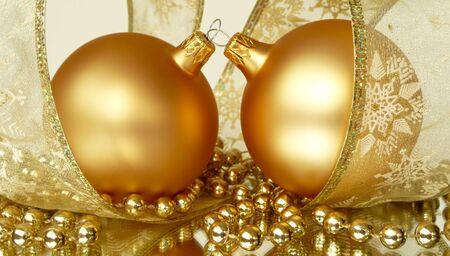 pair of gold christmas tree balls with  ribbon and string of beads