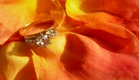 diamond engagement ring on bed of pastel rose petals Stock Photo