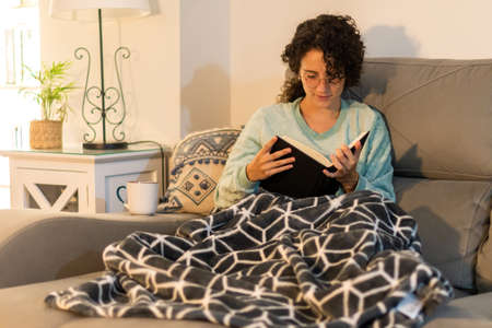 Stock photo of a beautiful young woman with curly hair and glasses reading a book at home, sitting on the coach. Curly girl with soft blanket and winter pajama reading on a winter afternoon.