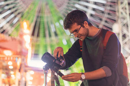 Portrait of a young men smiling and taking photos with a reflex camera and a tripod at a carnival fair at night. Young photographer with beard and glasses, with a ferris wheel in the background. Imagens