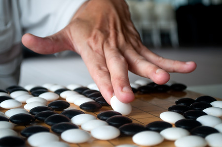 Cierre de blanco Ir jugador de la mano que muestra cómo sostener y colocar la pieza a bordo estaba llena. enfoque seleccionado.
