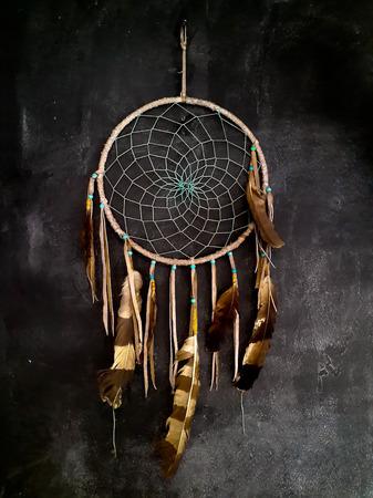 native culture: Dreamcatcher hanging on dark grey wall