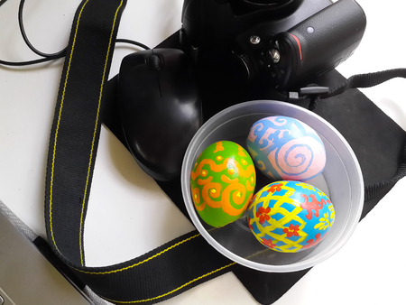 mouse pad: Easter eggs in plastic bowl along side black camera and black mouse on black mouse pad on white tabletop. Easter theme photographing preparation. Stock Photo