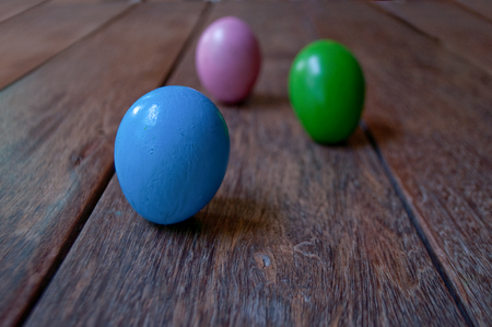 narrow depth of field: Easter eggs on brown wood plank floor. Narrow depth of field. Selected focus.
