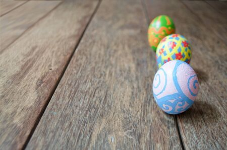 narrow depth of field: Easter eggs on brown wood plank floor. Homemade, hand painted. Narrow depth of field. Selected focus. Stock Photo