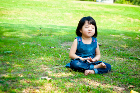 meditate: Little asian girl practicing mindfulness meditation outdoor in a park.